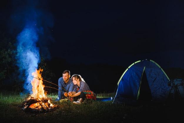 カップルが火でソーセージを焼き、夜の森のキャンプファイヤーでリラックス
