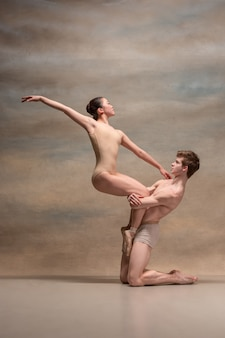 Couple of ballet dancers posing over gray space
