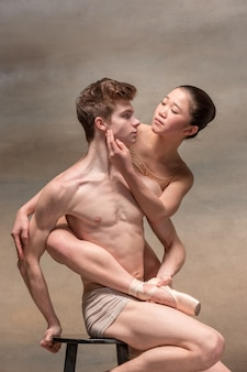 Couple of ballet dancers posing over gray.