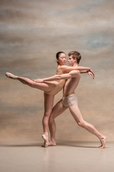 Couple of ballet dancers posing over gray