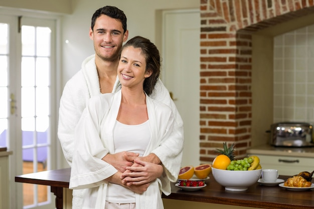 Couple in bathrobe smiling while embracing each other in kitchen