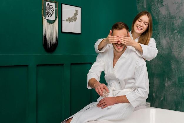 Couple in bathrobes on bathtub