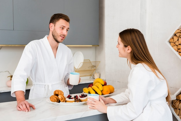 Couple in bathrobes having coffee in the kitchen