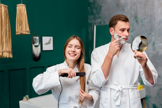 Couple in bathrobes shaving and straightening hair
