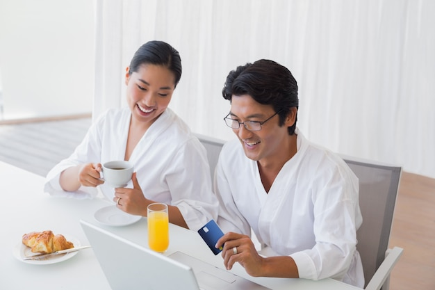 Couple in bathrobes shopping online in the morning