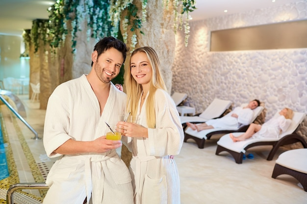 A couple in the bathrobes at the spa is resting.