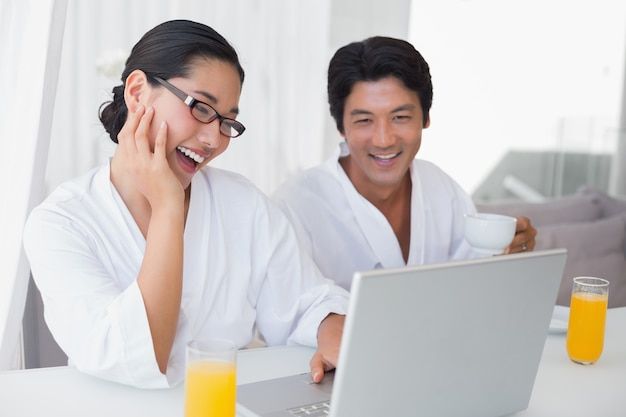 Couple in bathrobes spending the morning together using laptop