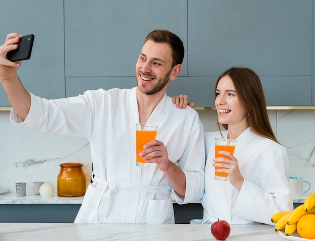 Couple in bathrobes taking a selfie with glasses of juice