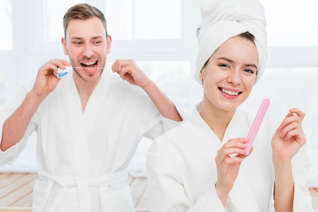 Couple in bathrobes using dental floss and nail file