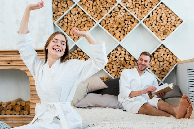 Couple in bathrobes waking up in bed