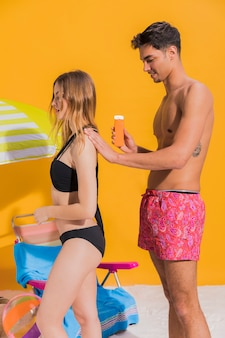 Couple on beach putting on sunblock