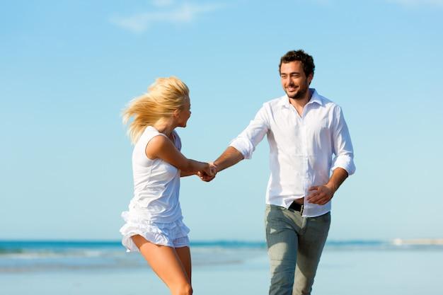 Couple on the beach running into glorious future