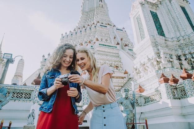 Couple of beautiful girls visiting bangkok maining attractions