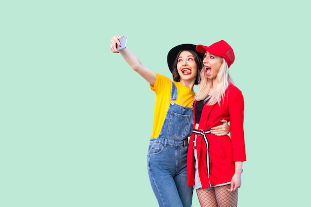 Couple of beautiful stilysh hipster best friends in fashionable clothes hugging with love, posing for camera and making selfie or live, showing tongue. indoor studio shot, isolated on green background