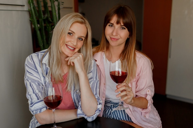 Couple of beautiful women drinking wine at home. wearing pajamas.