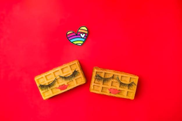 Пара красоты сладкие венские вафли с макияжем на красном фоне