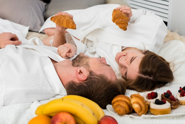 Couple in bed holding croissants