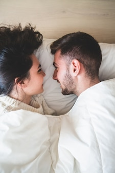 Couple in bed looking at each other and smiling