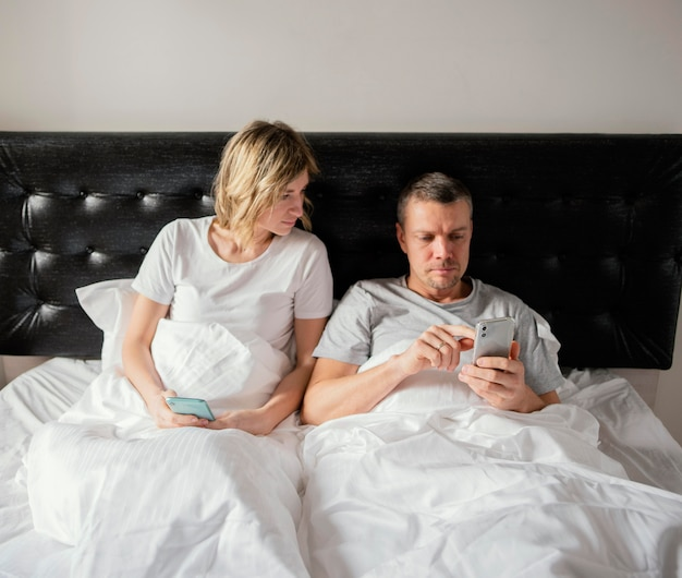 Couple in bed using mobiles