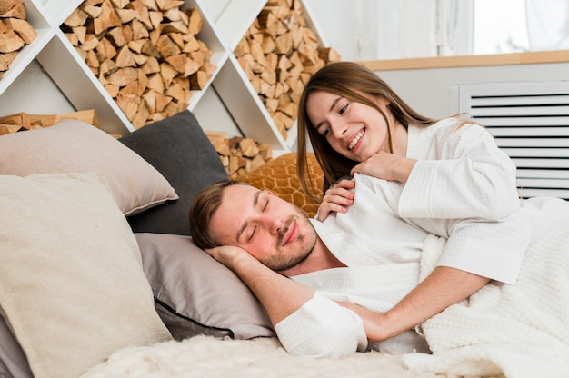 Couple in bed wearing bathrobes waking up