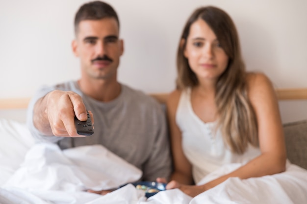 Couple in bed with remote control