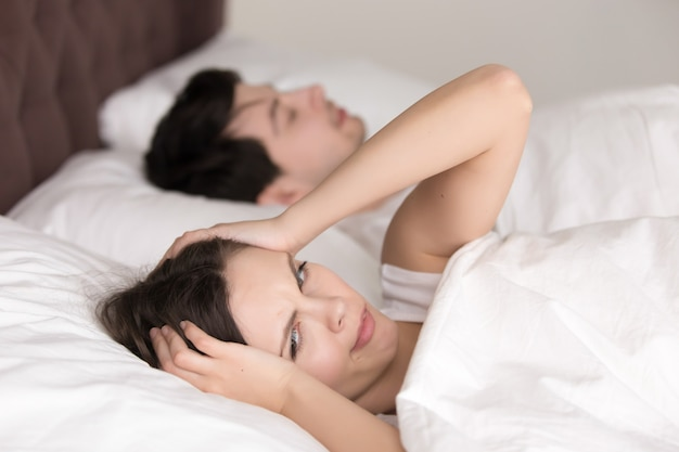 Couple in bed, woman suffering from insomnia, headache, snoring