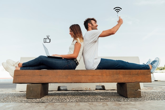 Couple on a bench using social media