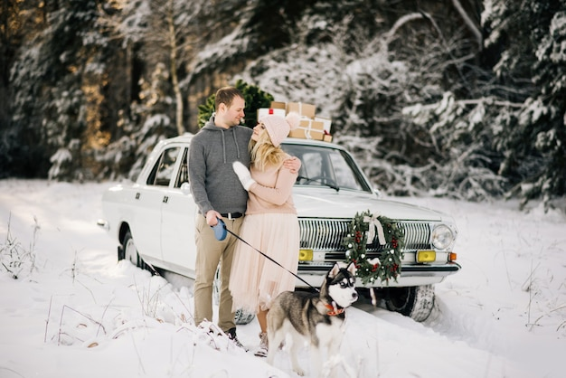 Couple beside car with husky in winter time