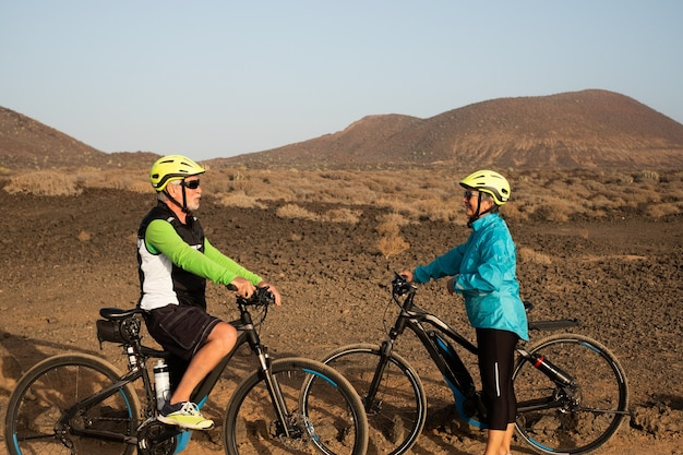 Couple of bikers meet outdoors enjoying exercise and excursion in a natural park