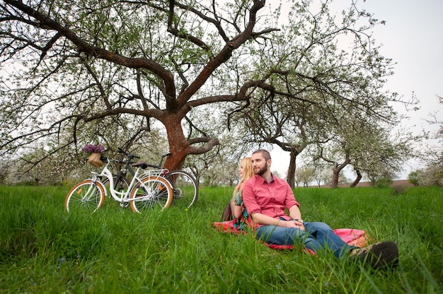 Couple of bikers sitting on blanket in the fresh green grass