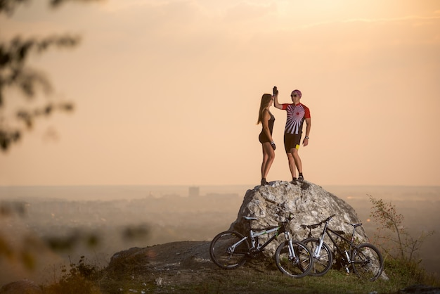 Couple bikers standing on a rock and giving high five at summer evening with blurred background.