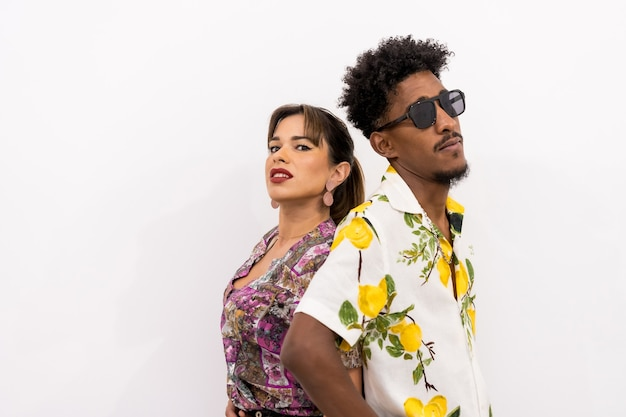 Couple of a black boy and a caucasian girl on a white background, flowery shirts, posed fashionably with their backs pressed together