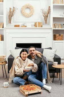 Couple in blanket eating pizza and popcorn