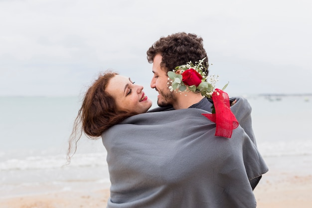 Couple in blanket hugging on sea shore
