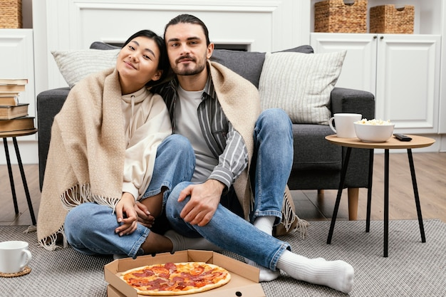 Couple in blanket watching tv and eating pizza