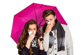 Couple blowing nose while holding umbrella