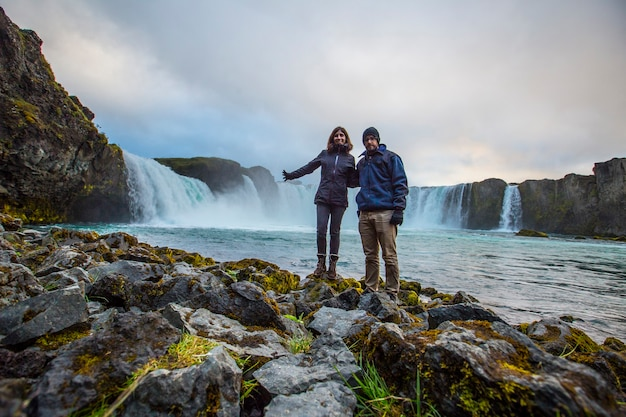 A couple at the bottom of the godafoss waterfall with sunset in the background, iceland