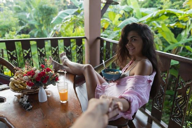 Couple breakfast, smiling woman eating muesli and drinking orange juice