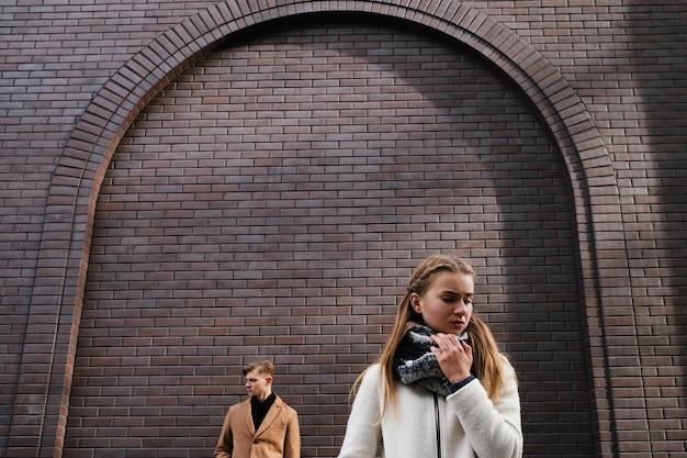 カップルの別れ。悲しい女の子。難しい関係。紛争問題の概念。レンガの壁の空き領域の背景