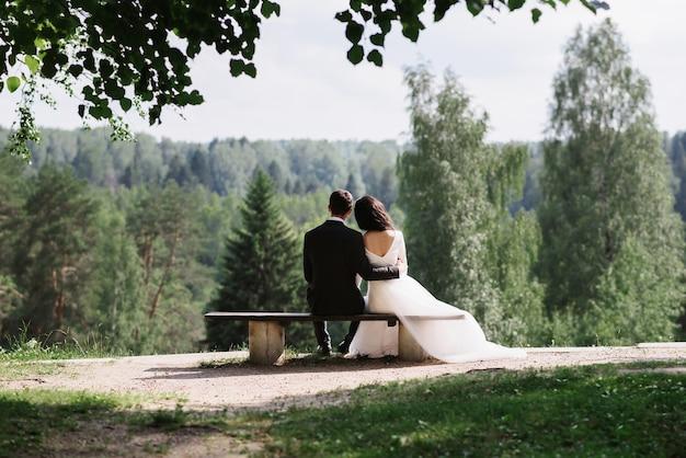 Пара невесты и жениха обнимаются, сидя на скамейке в день свадьбы летом на природе