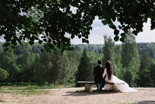 Пара жениха и невесты обнимаются, сидя на скамейке в день свадьбы летом на природе