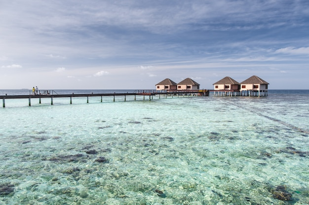 Couple on bridge to water villas on crystal clear water at tropical island