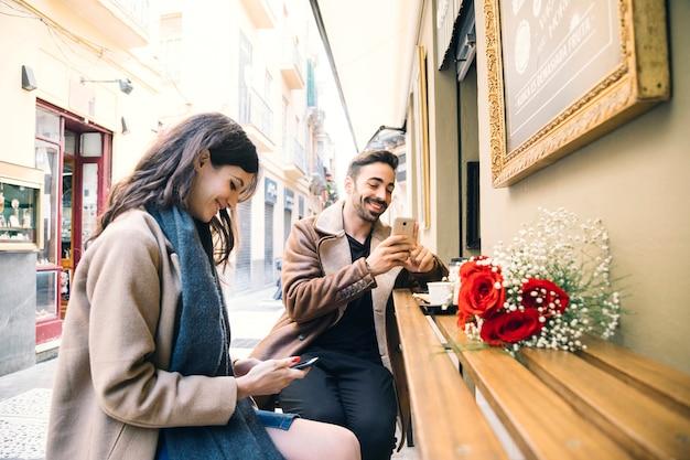 日付にスマートフォンを閲覧しているカップル