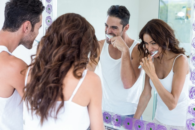 Couple brushing teeth while looking in mirror