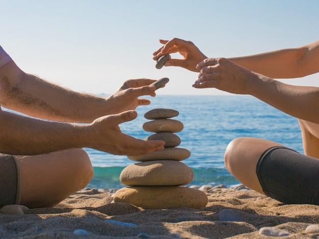 부부는 해변에 돌 피라미드를 구축합니다. 관계와 사랑의 개념