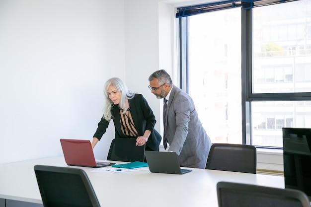 Coppia di colleghi di lavoro o partner che iniziano la riunione nella sala conferenze, in piedi al tavolo e utilizzando il computer portatile insieme. campo ampio. concetto di comunicazione aziendale