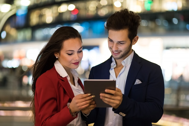 Couple of business people using a tablet outdoor at night in a modern city setting
