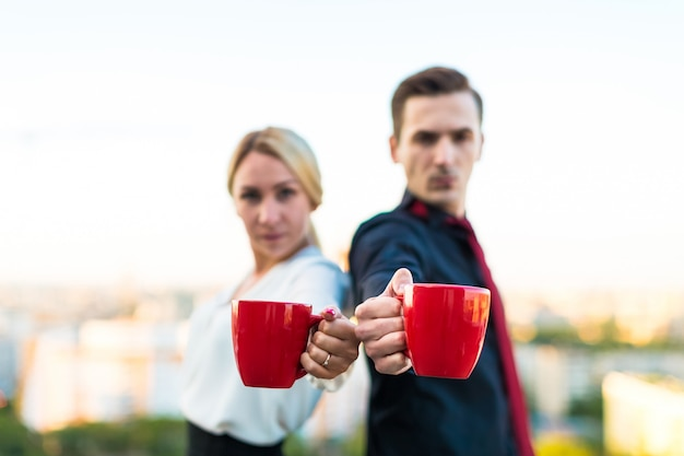 Couple of businessmen, attractive brunette man and pretty blonde woman stand on the roof and drink coffe