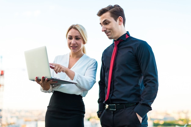 Couple of businessmen, serious brunette man and attractive blonde woman stand on the roof and look in laptop