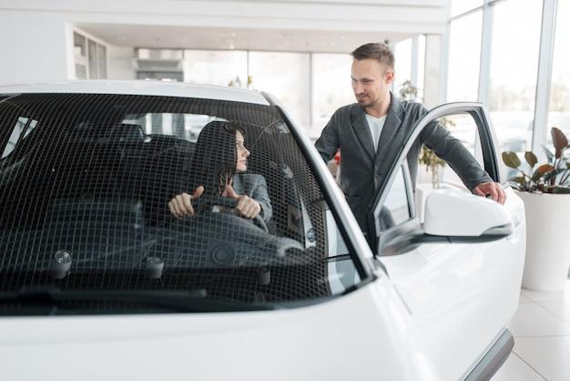 新しい車を買うカップル、ホイールの後ろの女性